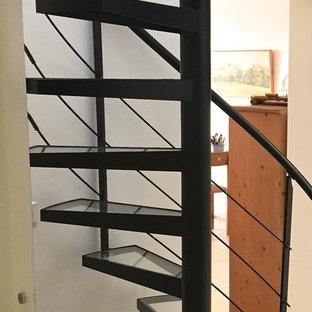 На фото: винтовая лестница в современном стиле с стеклянными ступенями без подступенок