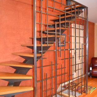 Idee per una scala curva minimalista di medie dimensioni con pedata in legno e parapetto in metallo