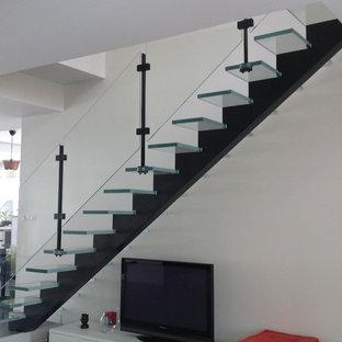 Ispirazione per una scala a rampa dritta contemporanea con pedata in vetro e nessuna alzata