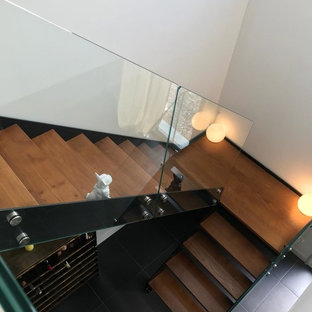 Large minimalist painted curved glass railing staircase photo in Lille with painted risers