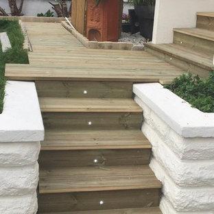 Inspiration pour un grand escalier craftsman en L avec des marches en bois, des contremarches en bois et un garde-corps en bois.