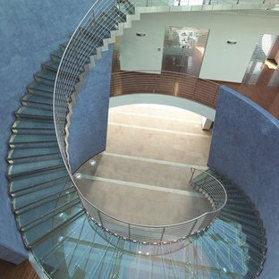 Huge trendy glass curved metal railing staircase photo in Paris with glass risers