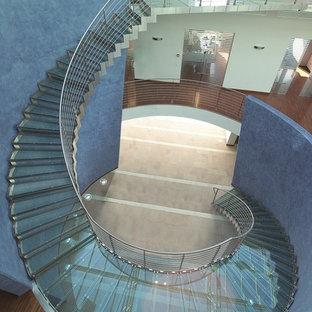 パリの巨大なガラスのコンテンポラリースタイルのおしゃれなサーキュラー階段 (ガラスの蹴込み板、金属の手すり) の写真