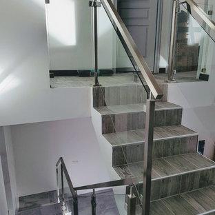 Diseño de escalera suspendida, minimalista, de tamaño medio, con escalones con baldosas, contrahuellas con baldosas y/o azulejos y barandilla de metal