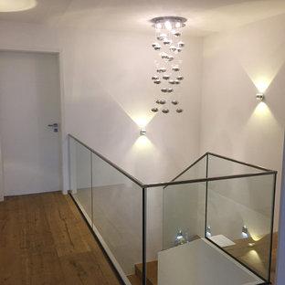 """Esempio di una scala a """"U"""" eclettica di medie dimensioni con pedata in legno, alzata in vetro e parapetto in vetro"""