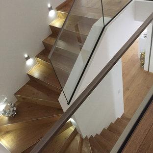 パリの中サイズの木のコンテンポラリースタイルのおしゃれな折り返し階段 (ガラスの蹴込み板、ガラスの手すり) の写真