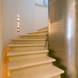 Foto di una grande scala curva design con pedata in pietra calcarea, alzata in pietra calcarea e parapetto in vetro