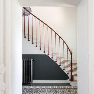 Modelo de escalera curva, moderna, pequeña, con escalones de madera, contrahuellas de madera pintada y barandilla de varios materiales