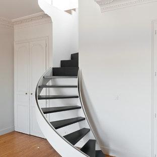 Modern inredning av en liten svängd trappa i målat trä, med öppna sättsteg