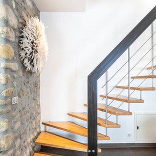 Cette photo montre un escalier sans contremarche tendance en L avec des marches en bois et un garde-corps en métal.