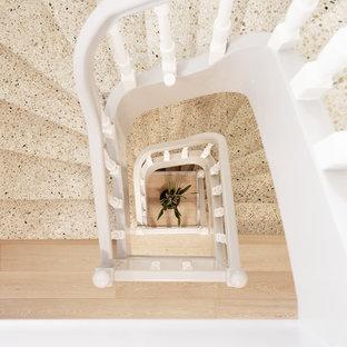 Foto di una scala a chiocciola contemporanea di medie dimensioni con pedata in pietra calcarea, alzata in pietra calcarea e parapetto in legno