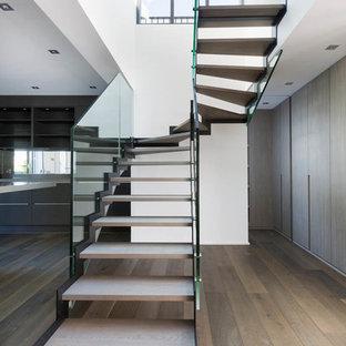 Ispirazione per una grande scala curva moderna con pedata in legno e nessuna alzata