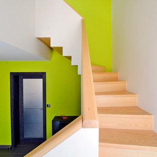 Aménagement d'un grand escalier courbe contemporain avec des marches en bois et des contremarches en bois.