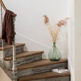Ispirazione per una scala curva di medie dimensioni con pedata in legno, alzata in legno e parapetto in metallo