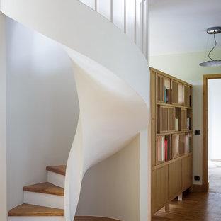 Idee per una scala a chiocciola minimal di medie dimensioni con pedata in legno e alzata in legno verniciato