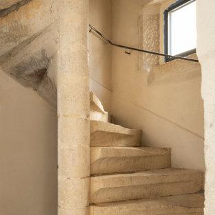 Ispirazione per una scala a chiocciola bohémian con pedata in pietra calcarea, alzata in pietra calcarea e parapetto in metallo