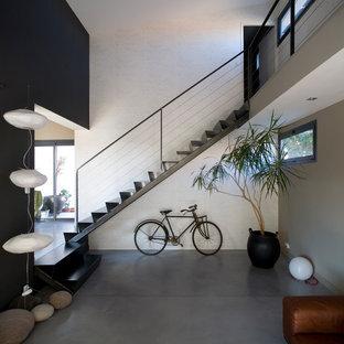Cette image montre un escalier droit design avec des marches en métal, des contremarches en métal et un garde-corps en câble.