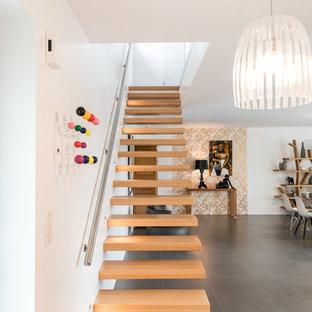 Foto de escalera recta, actual, grande, sin contrahuella, con escalones de madera y barandilla de metal