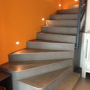 Foto di una scala minimalista con pedata in cemento, alzata in cemento e parapetto in metallo