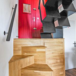 Foto de escalera curva, actual, pequeña, con escalones de madera, contrahuellas de madera y barandilla de metal