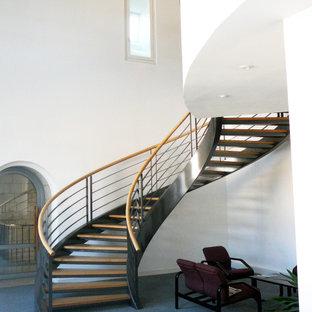 Idée de décoration pour un très grand escalier sans contremarche hélicoïdal méditerranéen avec des marches en bois et un garde-corps en matériaux mixtes.