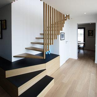 Modelo de escalera curva, contemporánea, grande, sin contrahuella, con escalones de madera y barandilla de madera