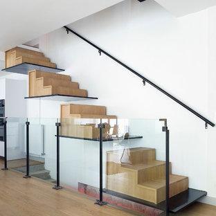 Cette image montre un grand escalier flottant design avec des marches en bois et des contremarches en bois.