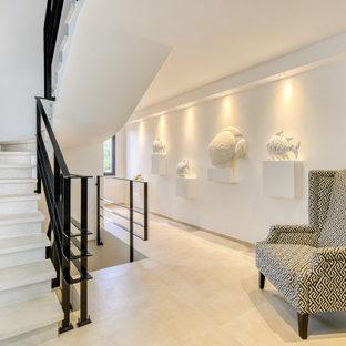 Diseño de escalera en U, actual, grande, con escalones de piedra caliza, contrahuellas de hormigón y barandilla de metal