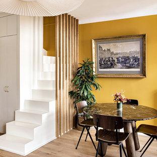 Bild på en mellanstor funkis svängd trappa i målat trä, med sättsteg i målat trä och räcke i trä