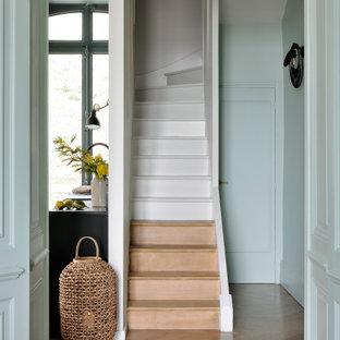 Cette image montre un escalier design en U de taille moyenne avec des marches en bois, des contremarches en bois et un garde-corps en matériaux mixtes.