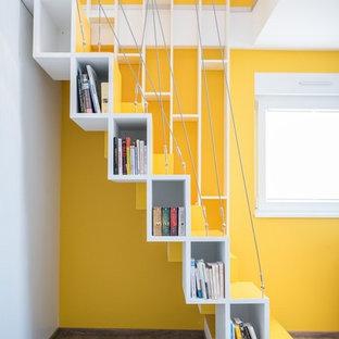 Foto de escalera recta, actual, de tamaño medio, con escalones de madera pintada, contrahuellas de madera pintada y barandilla de cable