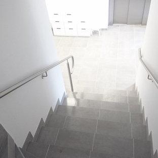 Foto de escalera recta, moderna, grande, con escalones de piedra caliza, contrahuellas de hormigón y barandilla de metal