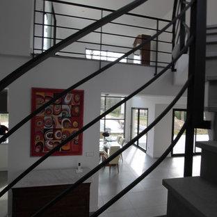 他の地域の中くらいのライムストーンのコンテンポラリースタイルのおしゃれなサーキュラー階段 (ライムストーンの蹴込み板、金属の手すり) の写真
