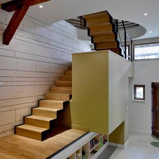 Idée de décoration pour un escalier design en U avec des marches en bois, des contremarches en bois et un garde-corps en métal.