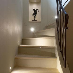 Foto de escalera clásica renovada, de tamaño medio, con escalones de piedra caliza, contrahuellas de hormigón y barandilla de metal