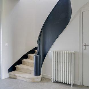 Bild på en mellanstor funkis svängd trappa i marmor, med sättsteg i marmor och räcke i flera material