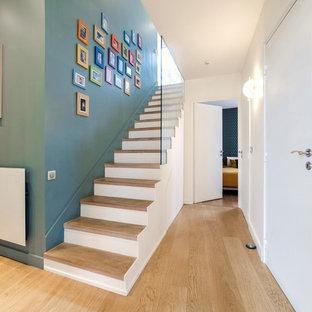 Inspiration pour un escalier droit nordique avec des marches en bois, des contremarches en béton et un garde-corps en verre.