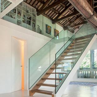 Foto di una scala a rampa dritta design con pedata in legno e nessuna alzata