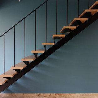 Ispirazione per una scala a rampa dritta country con pedata in legno e parapetto in metallo