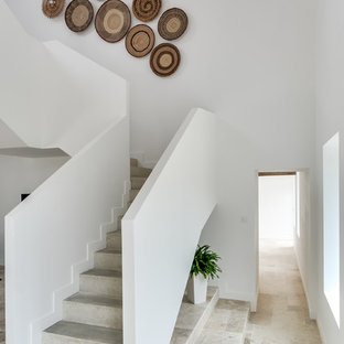 Staircase - mid-sized tropical concrete l-shaped staircase idea in Paris with concrete risers