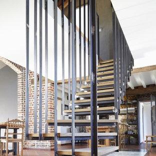 Exemple d'un grand escalier sans contremarche courbe nature avec des marches en bois.