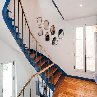 Modelo de escalera curva, tradicional renovada, con escalones de madera, contrahuellas de madera y barandilla de varios materiales