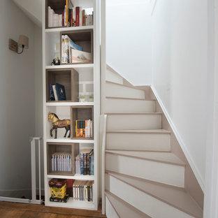 Cette photo montre un grand escalier courbe tendance avec des marches en bois peint et des contremarches en bois peint.