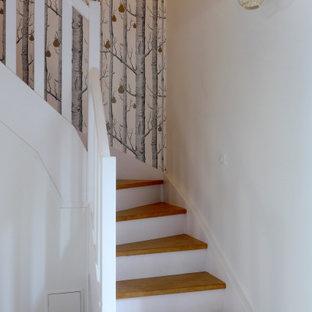 Exempel på en lantlig svängd trappa i trä, med sättsteg i målat trä och räcke i trä