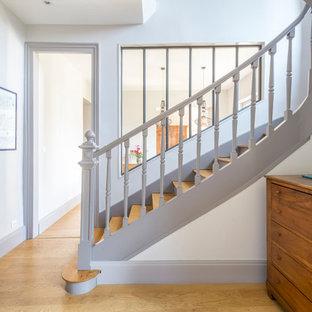 Cette image montre un escalier courbe traditionnel de taille moyenne avec des marches en bois, des contremarches en bois et un garde-corps en bois.