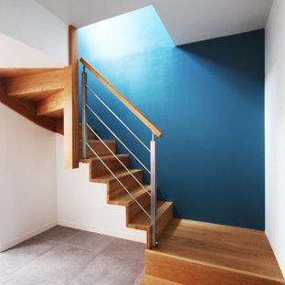 Inspiration pour un escalier courbe design de taille moyenne avec des marches en bois et des contremarches en bois.