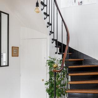 Exempel på en skandinavisk svängd trappa i trä, med sättsteg i målat trä och räcke i flera material