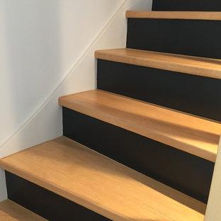 Foto de escalera en L, contemporánea, de tamaño medio, con escalones de madera, contrahuellas de madera pintada y barandilla de madera