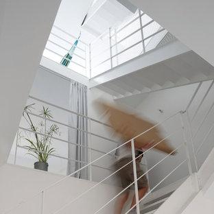 Réalisation d'un grand escalier sans contremarche design en U avec des marches en métal.