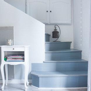 Exempel på en mellanstor shabby chic-inspirerad svängd trappa, med klinker och sättsteg i kakel